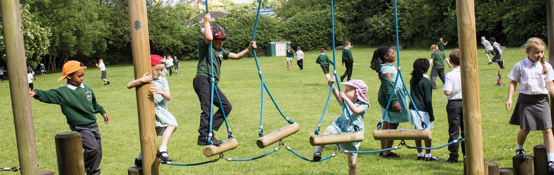 Children playing on wooden frame at corby old village primary school