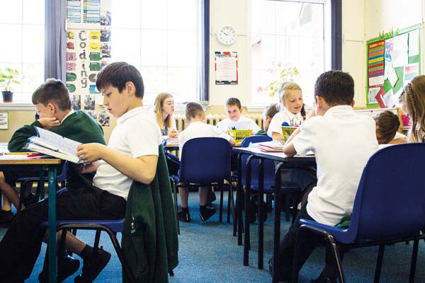 A classroom of children reading and writing