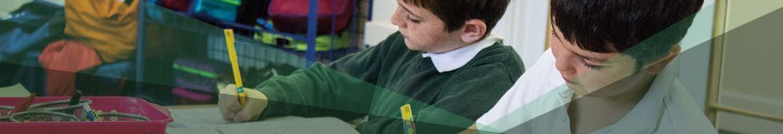 Two boys writing in class