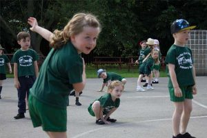 Children doing exercises on the playground during PE
