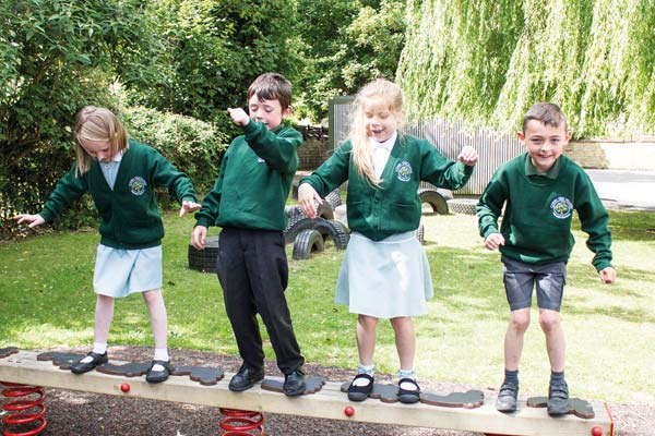 Children playing on a playground in Corby Old Village Primary School uniform